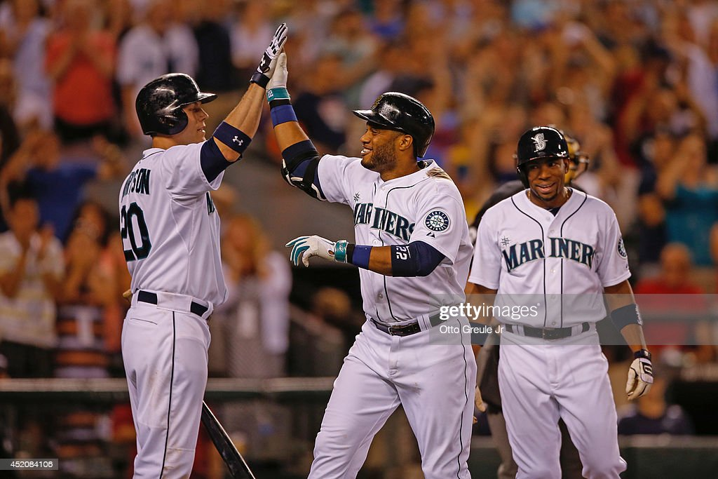 <a gi-track='captionPersonalityLinkClicked' href=/galleries/search?phrase=Robinson+Cano&family=editorial&specificpeople=538362 ng-click='$event.stopPropagation()'>Robinson Cano</a> #22 of the Seattle Mariners is congratulated by Logan Morrison #20 after hitting a three-run home run in the eighth inning against the Oakland Athletics at Safeco Field on July 12, 2014 in Seattle, Washington.