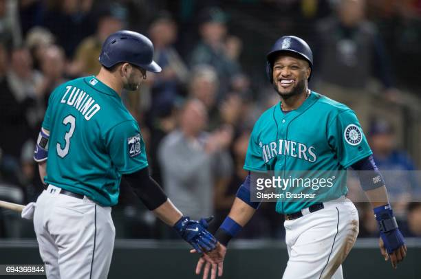 Robinson Cano of the Seattle Mariners is congratulated by Mike Zunino of the Seattle Mariners after scoring a run on single by Danny Valencia of the...