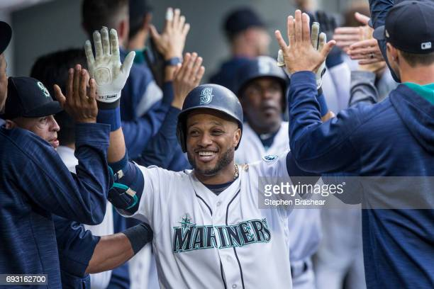 Robinson Cano of the Seattle Mariners is congratulated by teammates in the dugout after hitting a threerun home run off of starting pitcher Hector...