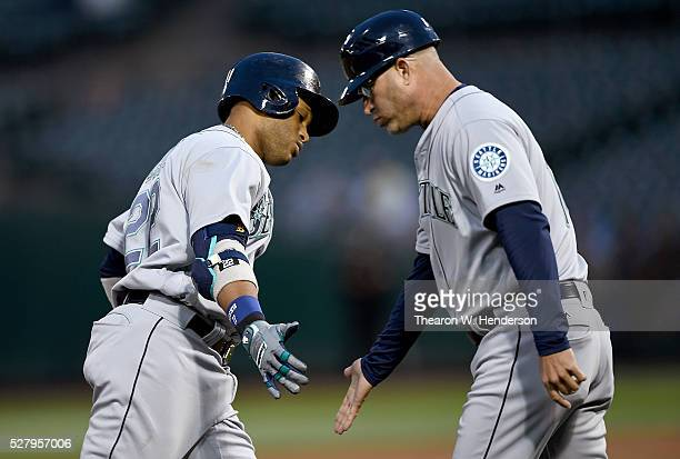 Robinson Cano of the Seattle Mariners is congratulated by third base coach after Cano hit a solo home run against the Oakland Athletics in the top of...