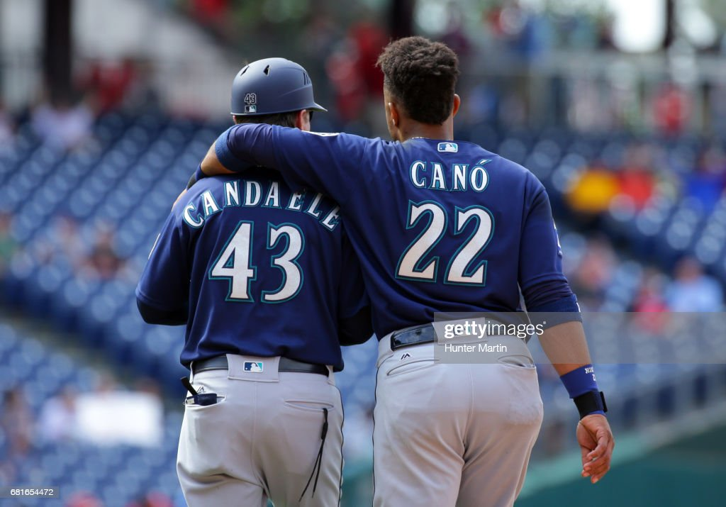 Robinson Cano #22 of the Seattle Mariners puts his arm around first base coach Casey Candaele #43 at the end of the seventh inning during a game against the Philadelphia Phillies at Citizens Bank Park on May 10, 2017 in Philadelphia, Pennsylvania. The Mariners won 11-6.