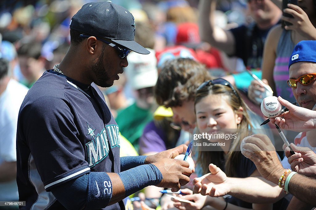 Robinson Cano #22 of the Seattle Mariners signs autographs for fans before the game against the Chicago Cubs at Cubs Park on March 20, 2014 in Mesa, Arizona.