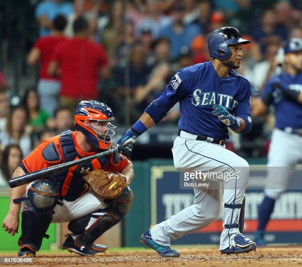 Robinson Cano of the Seattle Mariners singles in the fourth inning as Evan Gattis of the Houston Astros looks on at Minute Maid Park on September 15...