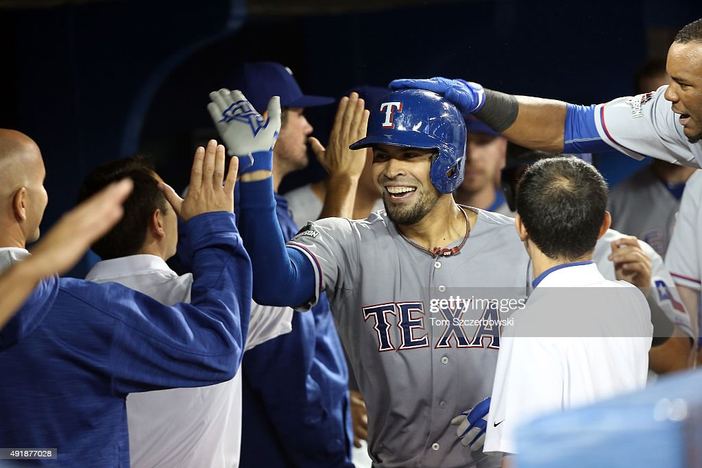 Robinson Chirinos #61 of the Texas Rangers celebrates in the dugout with his teammates after hitting a two run home run to left center field against David Price #14 of the Toronto Blue Jays in the fifth inning during game one of the American League Division Series at Rogers Centre on October 8, 2015 in Toronto, Ontario, Canada.