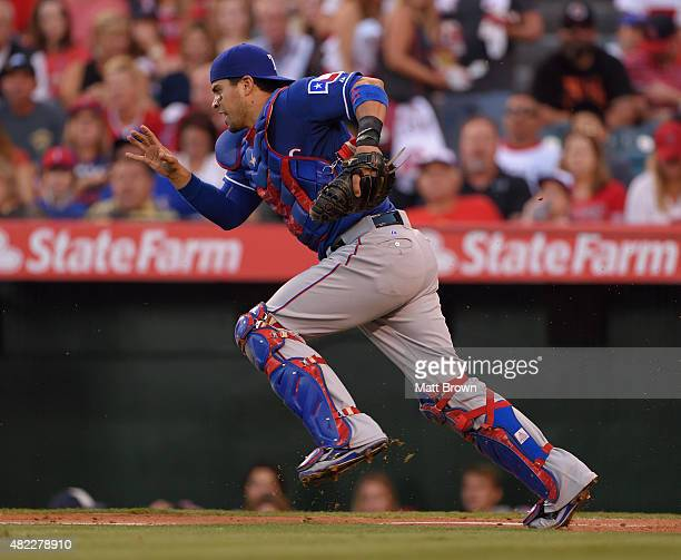 Robinson Chirinos of the Texas Rangers chases down a ground ball during the game against the Los Angeles Angels of Anaheim at Angel Stadium of...