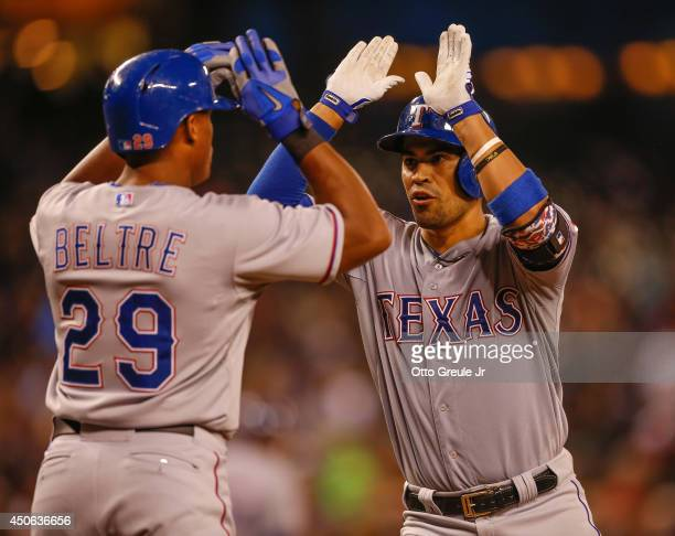 Robinson Chirinos of the Texas Rangers is congratulated by Adrian Beltre after hitting a tworun home run in the sixth inning against the Seattle...