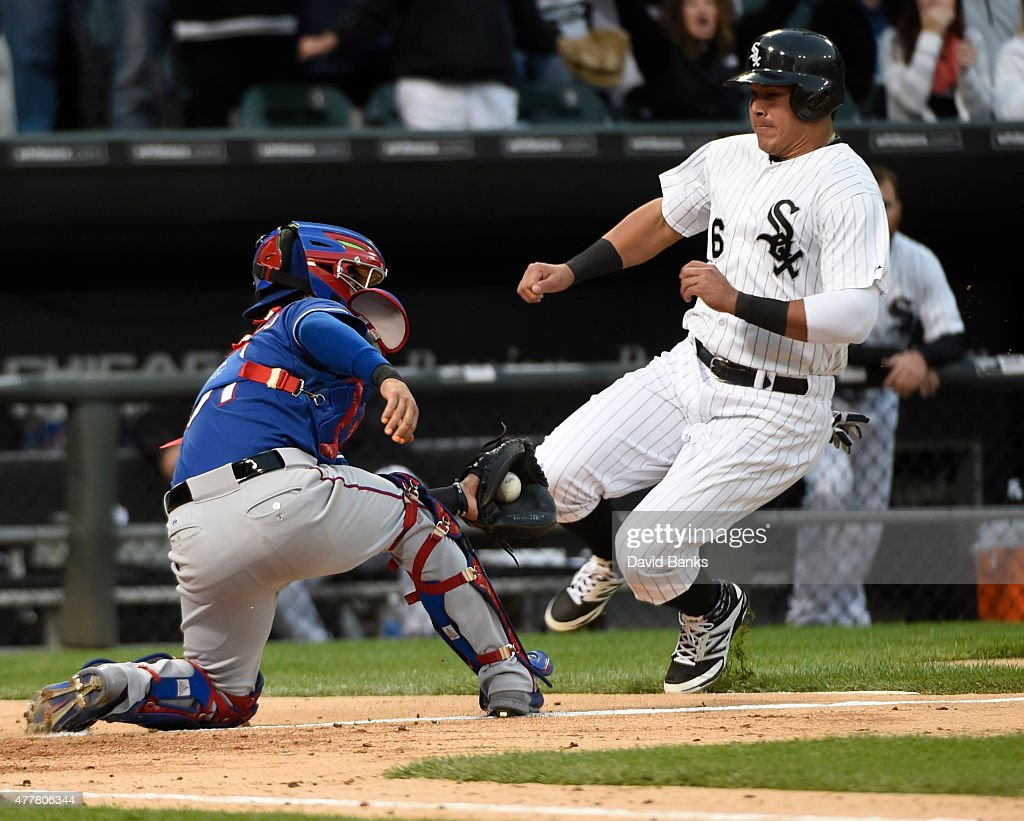 Robinson Chirinos #61 of the Texas Rangers prepares to tags out Avisail Garcia #26 of the Chicago White Sox at home plate during the fourth inning on June 19, 2015 at U. S. Cellular Field in Chicago, Illinois.