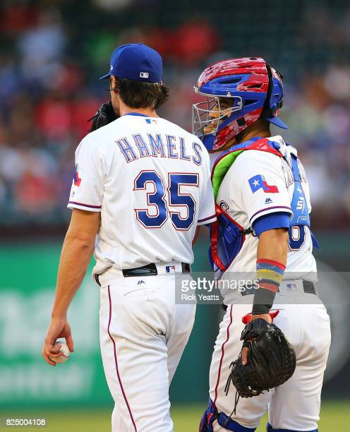 Robinson Chirinos of the Texas Rangers talks with Cole Hamels during in the third inning against the Seattle Mariners at Globe Life Park in Arlington...