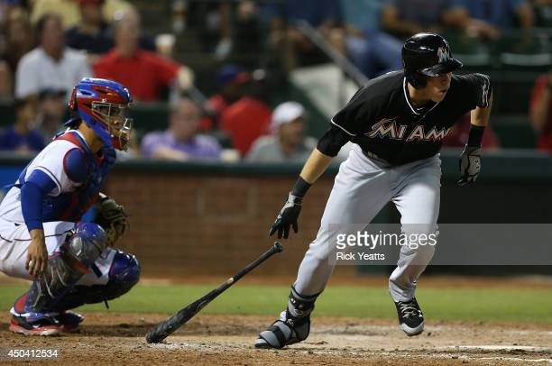 Robinson Chirinos of the Texas Rangers watches as Christian Yelich of the Miami Marlins hitting a double in the sixth inning at Globe Life Park in...