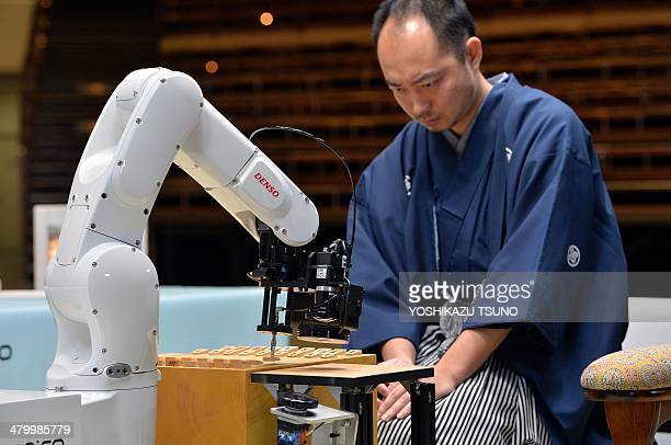 A robot arm developed by Japanese auto parts maker Denso and operated by computer game software YaneuraOu plays against professional shogi or...