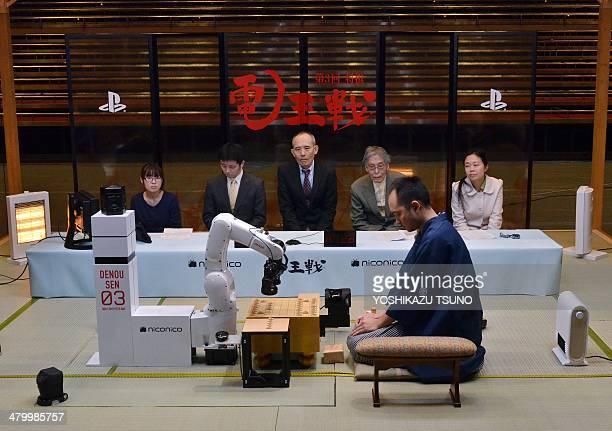 A robot arm developed by Jpanese auto parts maker Denso and operated by computer game software YaneuraOu sets pieces to play against professional...