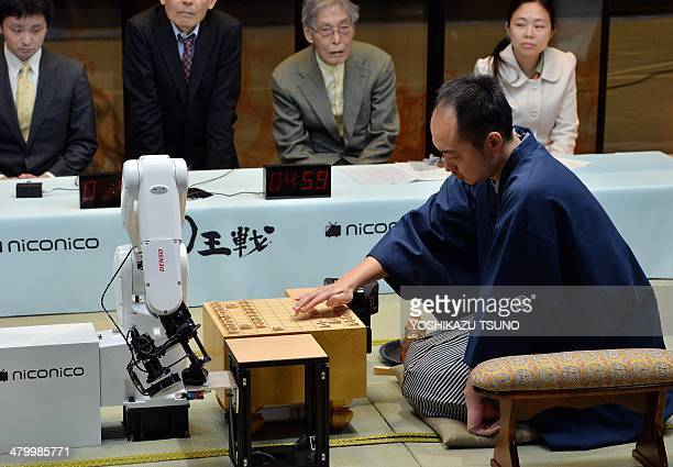 A robot arm developed by Jpanese auto parts maker Denso and operated by computer game software YaneuraOu plays against professional shogi or Japanese...