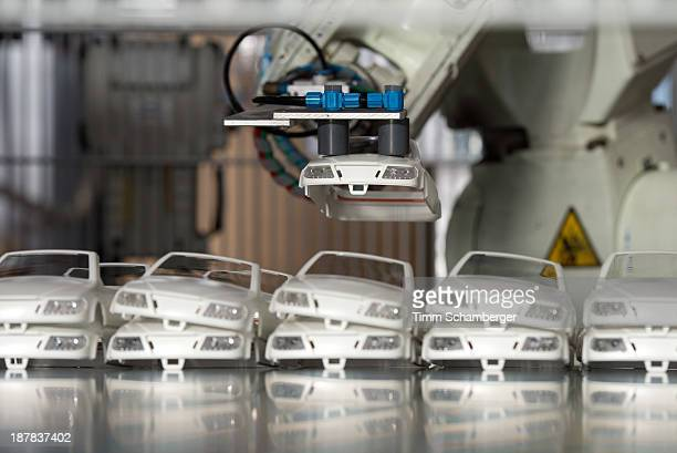 A robot arm of an injection molding machine puts a part of a toy car on a treadmill at the playmobil toy factory in Dietenhofen on November 12 2013...