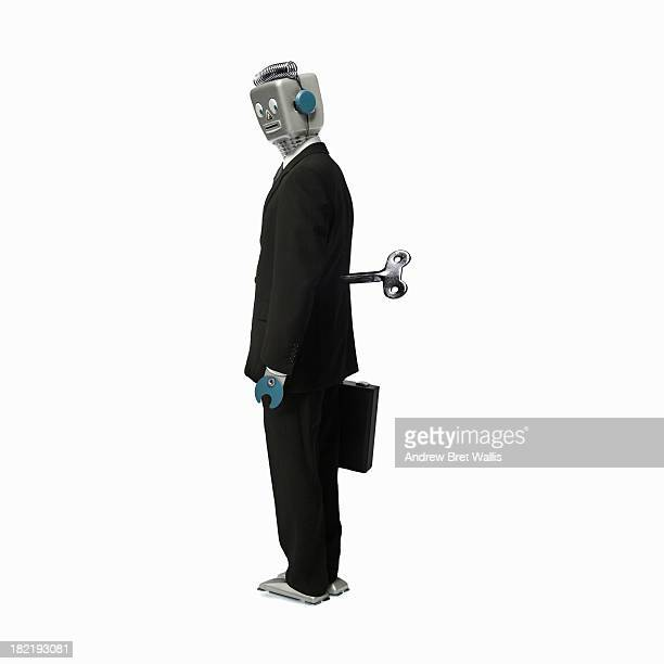 Robot businessman stands with a key in his back