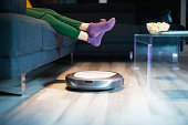 Young girl eating popcorn during movie night. Kid watches television on sofa. The child lifts feet up when a round robot vacuum cleaner passes to clean the dirty floor.