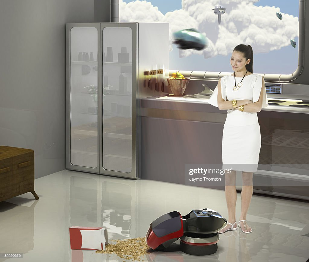 Robot cleaning up spill in future home : Stock Photo