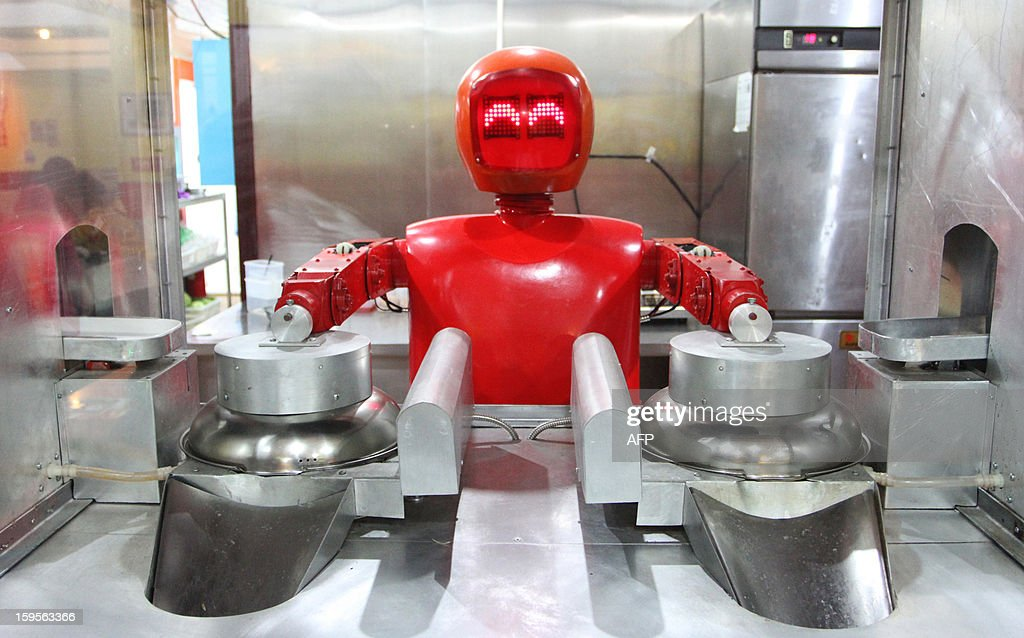 A robot cooks in a robot-themed restaurant in Harbin, northeast China's Heilongjiang province on January 16, 2013. Twenty robots perform a variety of chores, from ushering in guests to waiting tables and cooking dishes. CHINA