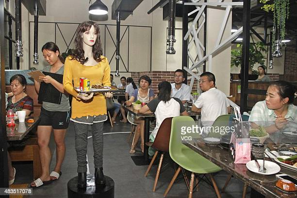 A robot delivers meals at a restaurant on August 3 2015 in Yiwu Zhejiang Province of China Kewang Trade Corporation spent three year to invent...