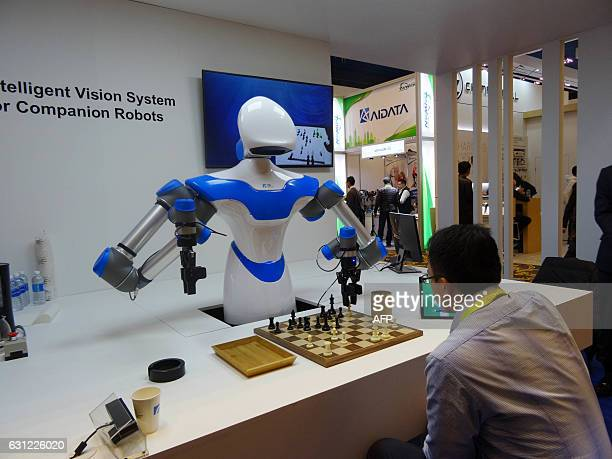 A robot developed by Taiwan engineers moves chess pieces on a board against an opponent at the 2017 Consumer Electronic Show in Las Vegas Nevada on...
