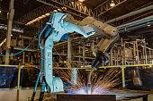 Robot is welding metal part in car factory