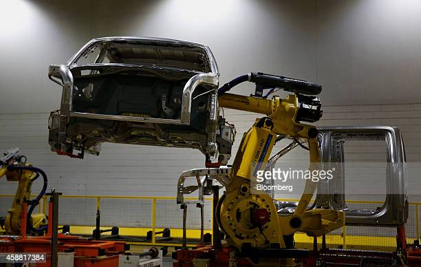 A robot moves a 2015 Ford Motor Co F150 truck on the production line at the company's Dearborn Truck Assembly facility in Dearborn Michigan US on...