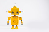 Cute, yellow, handmade robot on a white background.