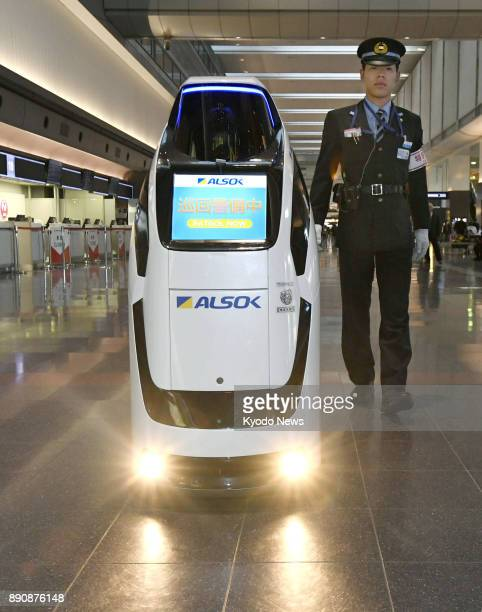 A robot proceeds along a concourse at Haneda airport in Tokyo on Dec 12 2017 The robot equipped with builtin cameras and sensors can patrol around...