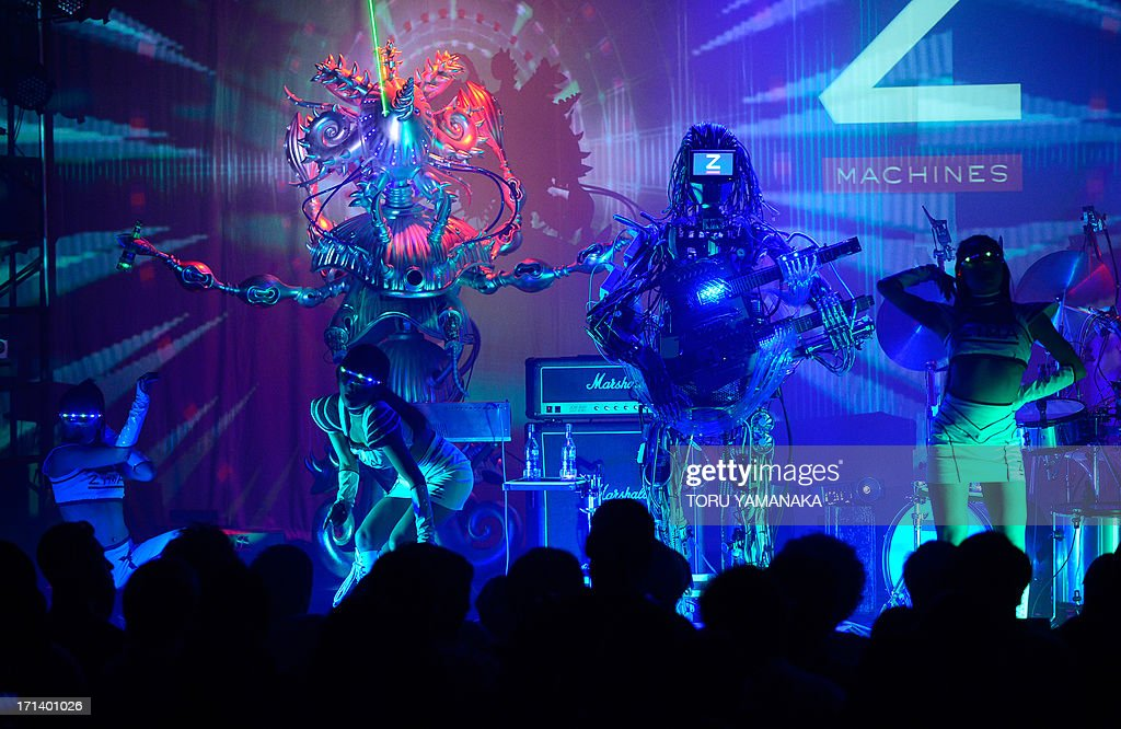 Robot rock band 'Z-MACHINES' performs with dancers during its debut concert in Tokyo on June 24, 2013. The robot band consists guitar robot 'Mach', drum robot 'Ashura' and keyboard robot 'Cosmo'. AFP PHOTO/Toru YAMANAKA