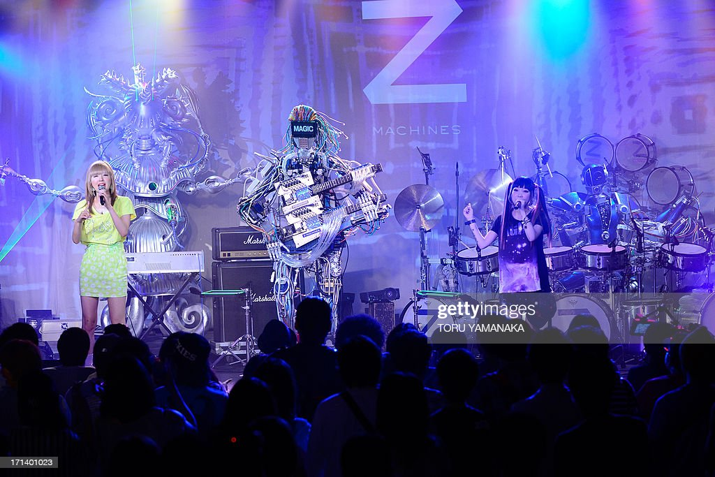 Robot rock band 'Z-MACHINES' performs with Japanese pop duo AMOYAMO during its debut concert in Tokyo on June 24, 2013. The robot band consists guitar robot 'Mach', drum robot 'Ashura' and keyboard robot 'Cosmo'. AFP PHOTO/Toru YAMANAKA