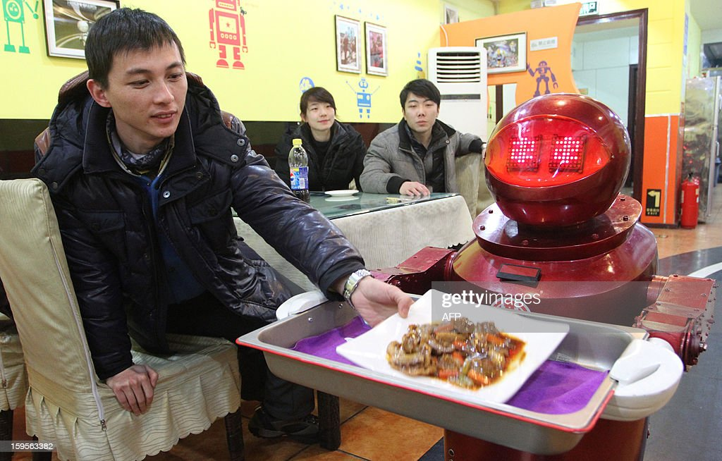 A robot serves guests in a robot-themed restaurant in Harbin, northeast China's Heilongjiang province on January 16, 2013. Twenty robots perform a variety of chores, from ushering in guests to waiting tables and cooking dishes. CHINA