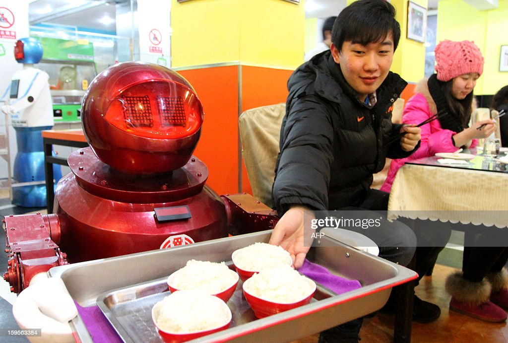 A robot serves rice to guests in a robot-themed restaurant in Harbin, northeast China's Heilongjiang province on January 16, 2013. Twenty robots perform a variety of chores, from ushering in guests to waiting tables and cooking dishes. CHINA OUT AFP PHOTO