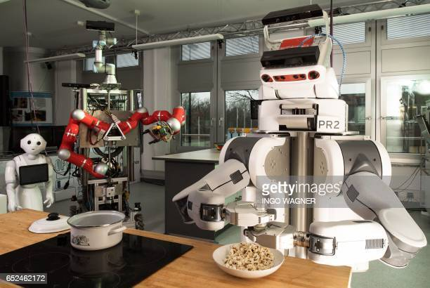A robot shakes salt over popcorn on March 8 2017 at the Institute for Artificial Intelligence of the university of Bremen northwestern Germany...