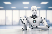 3d rendering humanoid robot sitting behind table on white background