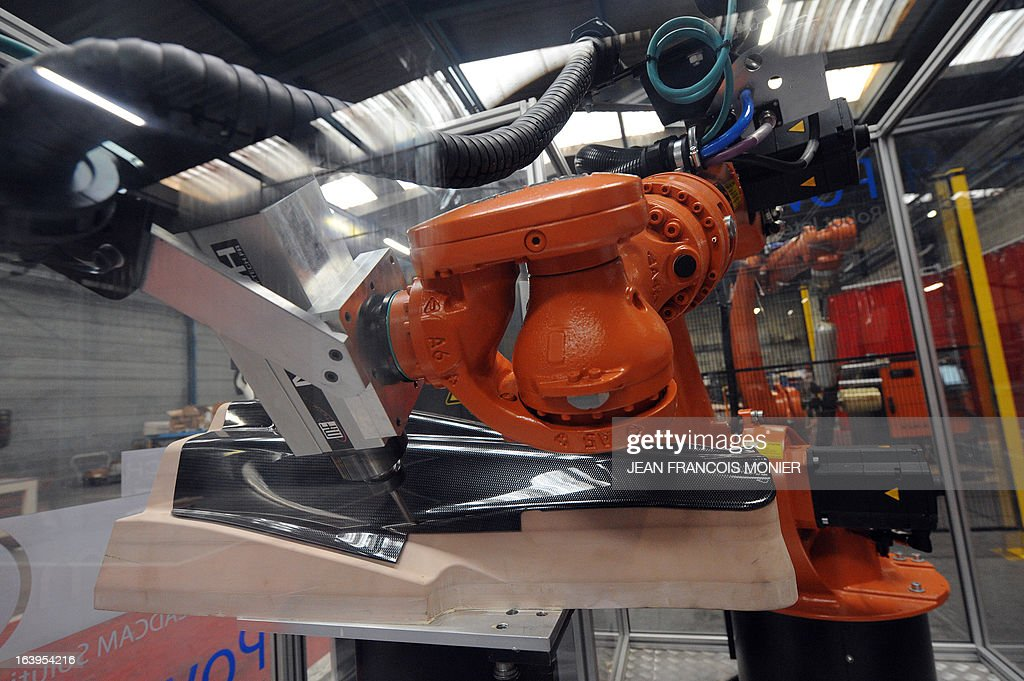 A robot trims composite parts for an automobile on March 18, 2013 at the MF Tech, composites consultants, plant in Argentan.