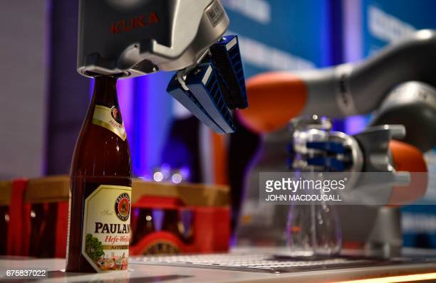 A robotic arm by German industrial robot manufacturer Kuka decapsulates a beer bottle as another one rinses a glass before pouring a beer for guests...