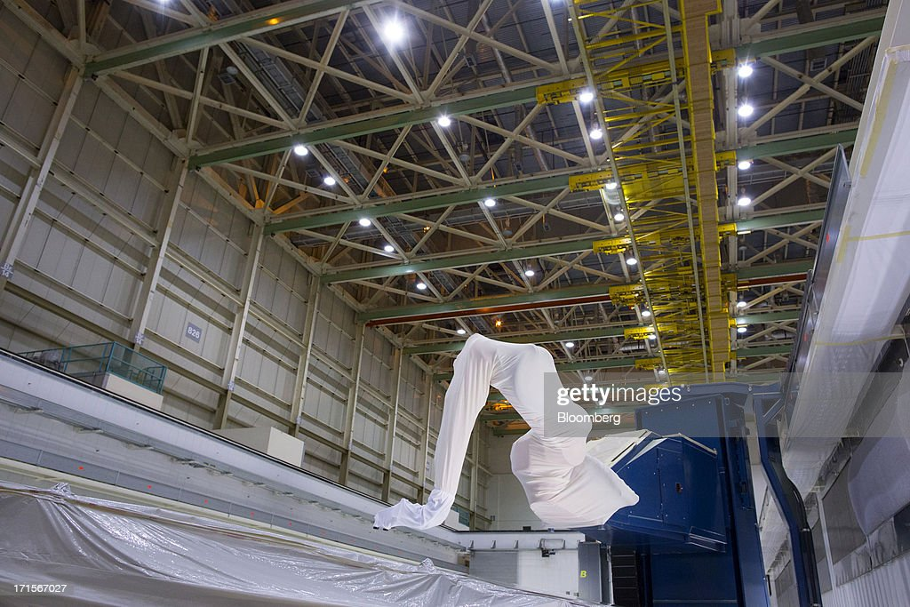 A robotic arm equipped with paint sprayers moves over the top of a 777 wing in a paint booth featuring the new ASM (automated spray method) technology at Boeing's Everett Factory in Everett, Wash. on Tuesday, June 25, 2013.