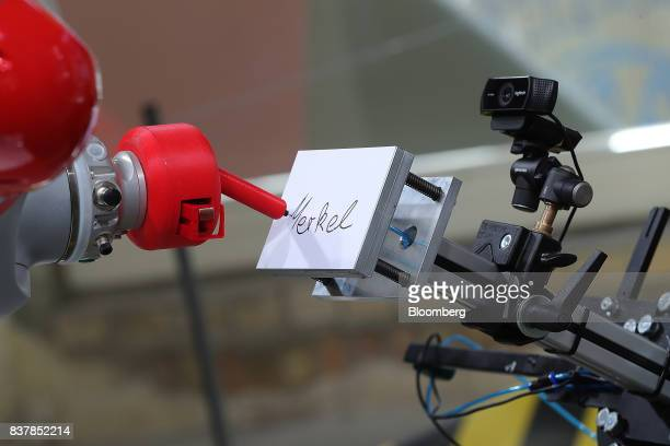 A robotic arm manufactured by Kuka AG writes 'Merkel' on a sticky note pad at an interactive display inside the Christian Democratic Union walkin...