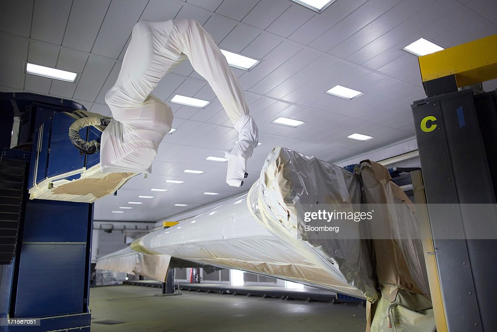 A robotic arm paints the top of a Boeing Co. 777 wing using the new Automated Spray Method (ASM) technology at the company's facility in Everett, Washington, U.S., on Tuesday, June 25, 2013. Boeing Co. uses the Automated Spray Method (ASM), which consists of a robot with two guns that applies two paints at different thicknesses, to efficiently paint the wings of the popular 777 airplanes. Photographer: Mike Kane/Bloomberg via Getty Images