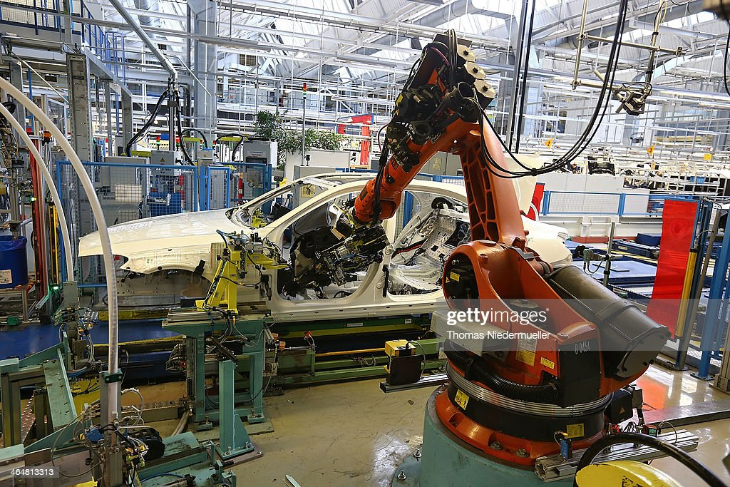 AG robotic arm prepares to install the cockpit section of a Daimler AG MercedesBenz SClass sedans on the assembly line at the MercedesBenz plant of...