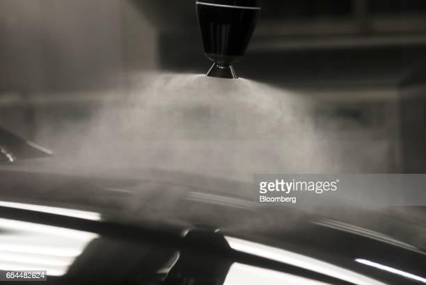 A robotic arm sprays paint onto the body of a Jaguar XJ automobile in the paint shop at Tata Motors Ltd's Jaguar assembly plant in Castle Bromwich UK...