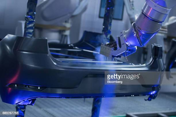 A robotic arm uses high pressure carbon dioxide gas to clean a plastic automobile bumper ahead of painting in the Volkswagen AG factory as part of...