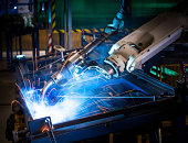 Robot arm welding uses torch to make sparks during manufacture of metal equipment.