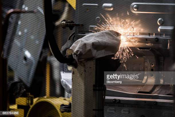 A robotic arm welds the body shells of an automobile on the production line inside the Suzuki Motor Corp plant in Esztergom Hungary on Monday May 15...