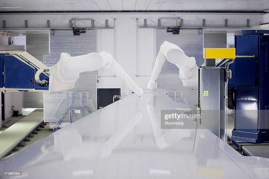 Robotic arms equipped with paint sprayers move over the top of a 777 wing in a paint booth featuring the new ASM (automated spray method) technology at Boeing's Everett Factory in Everett, Wash. on Tuesday, June 25, 2013.