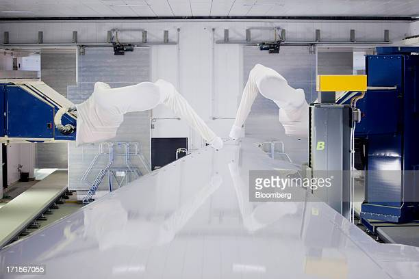 Robotic arms equipped with paint sprayers move over the top of a 777 wing in a paint booth featuring the new ASM technology at Boeing's Everett...