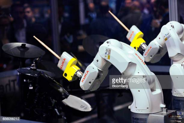 Robotic arms made by Kuka AG play the drums using drumsticks in a soundproof box at the CeBIT 2017 tech fair in Hannover Germany on Tuesday March 21...