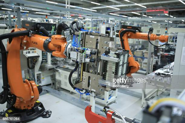 Robotic arms manufactured by Kuka AG move battery cell units along the assembly line at the Deutsche Accumotive GmbH electric automobile battery...