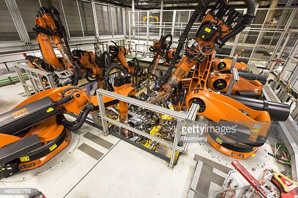 Robotic arms manufactured by Kuka AG operate on the undercarriage and side frame of a BMW automobile as it sits on the production line at the...