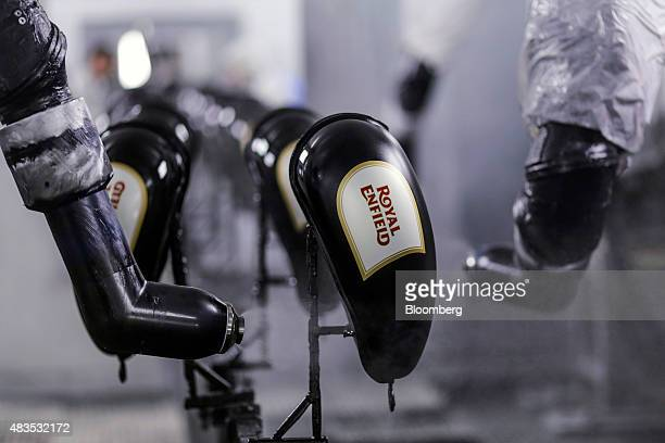Robotic arms spray lacquer onto gas tanks for the Royal Enfield Motors Ltd Classic 350 motorcycle as they move on a conveyor on the production line...