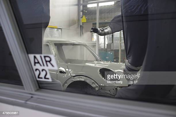 Robotic arms spray paint onto the body shell of a Mini Hatch automobile produced by Bayerische Motoren Werke AG in the paint shop of the VDL Nedcar...